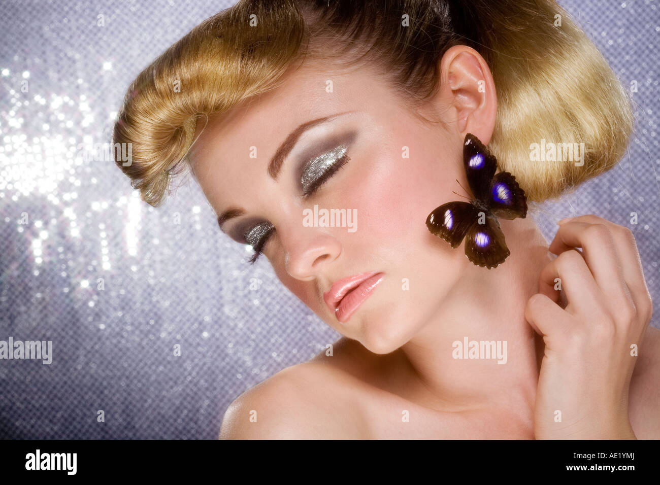 A portrait beautiful, glamorous young girl with a butterfly on her face. Stock Photo