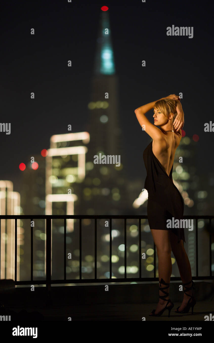 A young woman standing on a rooftop overlooking a brightly lit city skyline. Stock Photo