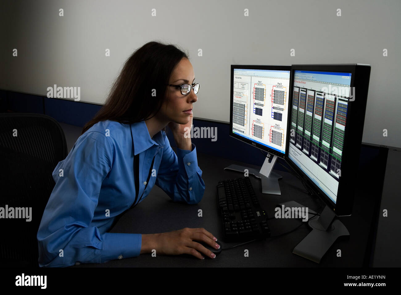 A woman sitting at a desk working on a two monitor computer system. Stock Photo