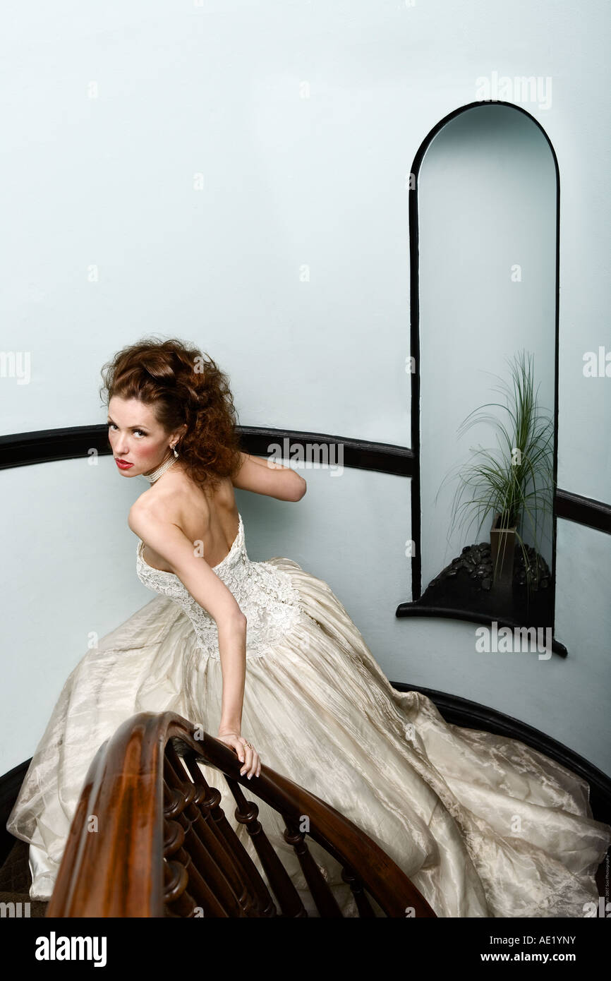 A beautiful bride descends down a staircase wearing a couture dress. Stock Photo