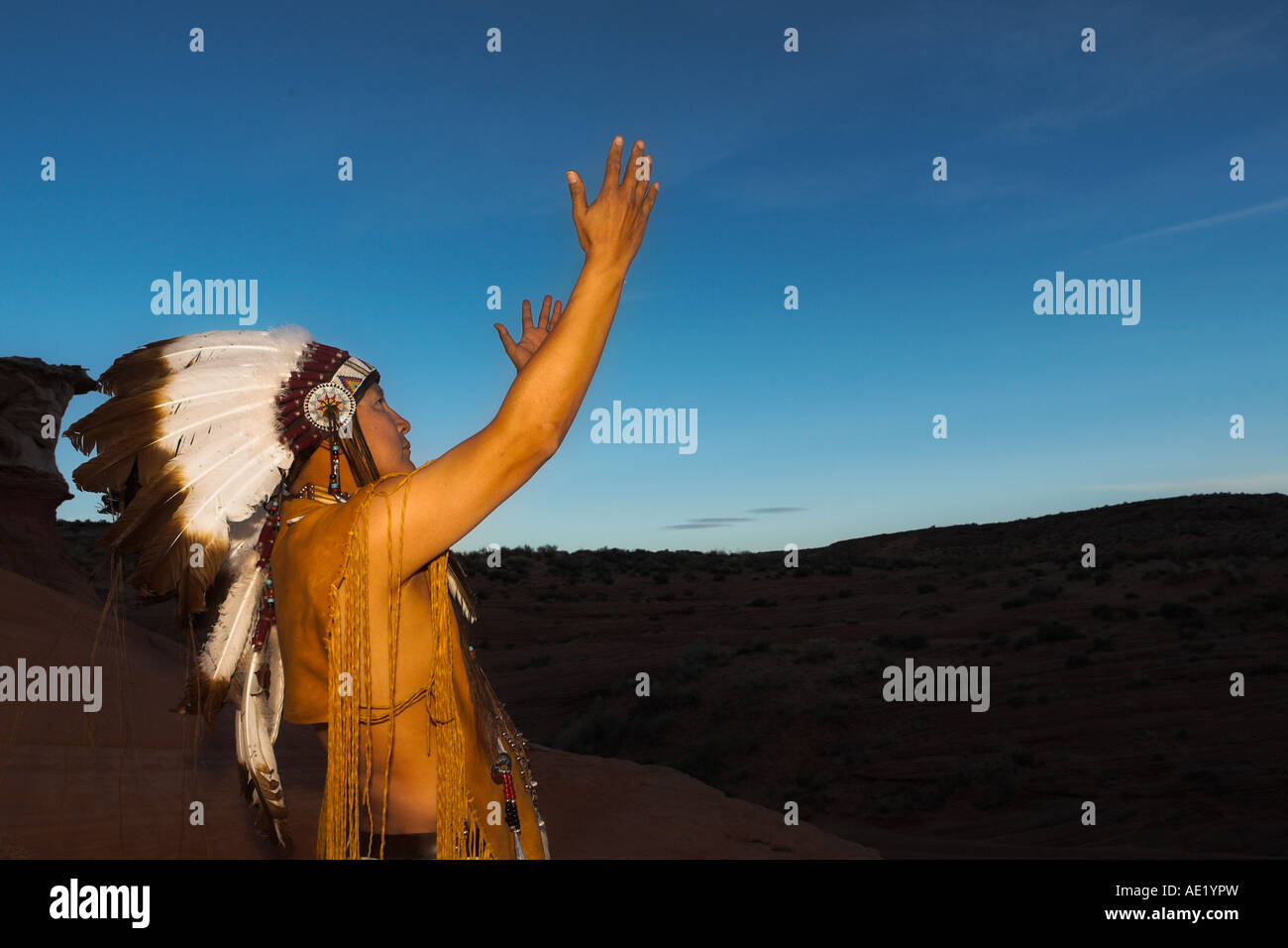Native American Indian man with cultural outfit uniform headdress feathers design patterns leather band nature sunset - Stock Image