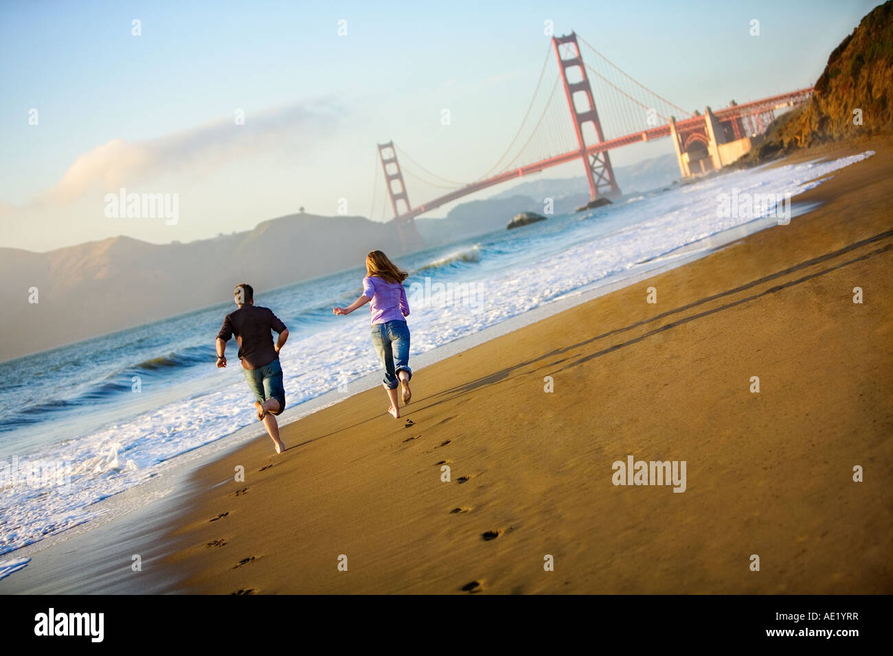 A couple running on the beach towards the golden gate bridge leaving footprints on the golden sand beach and ocean - Stock Image
