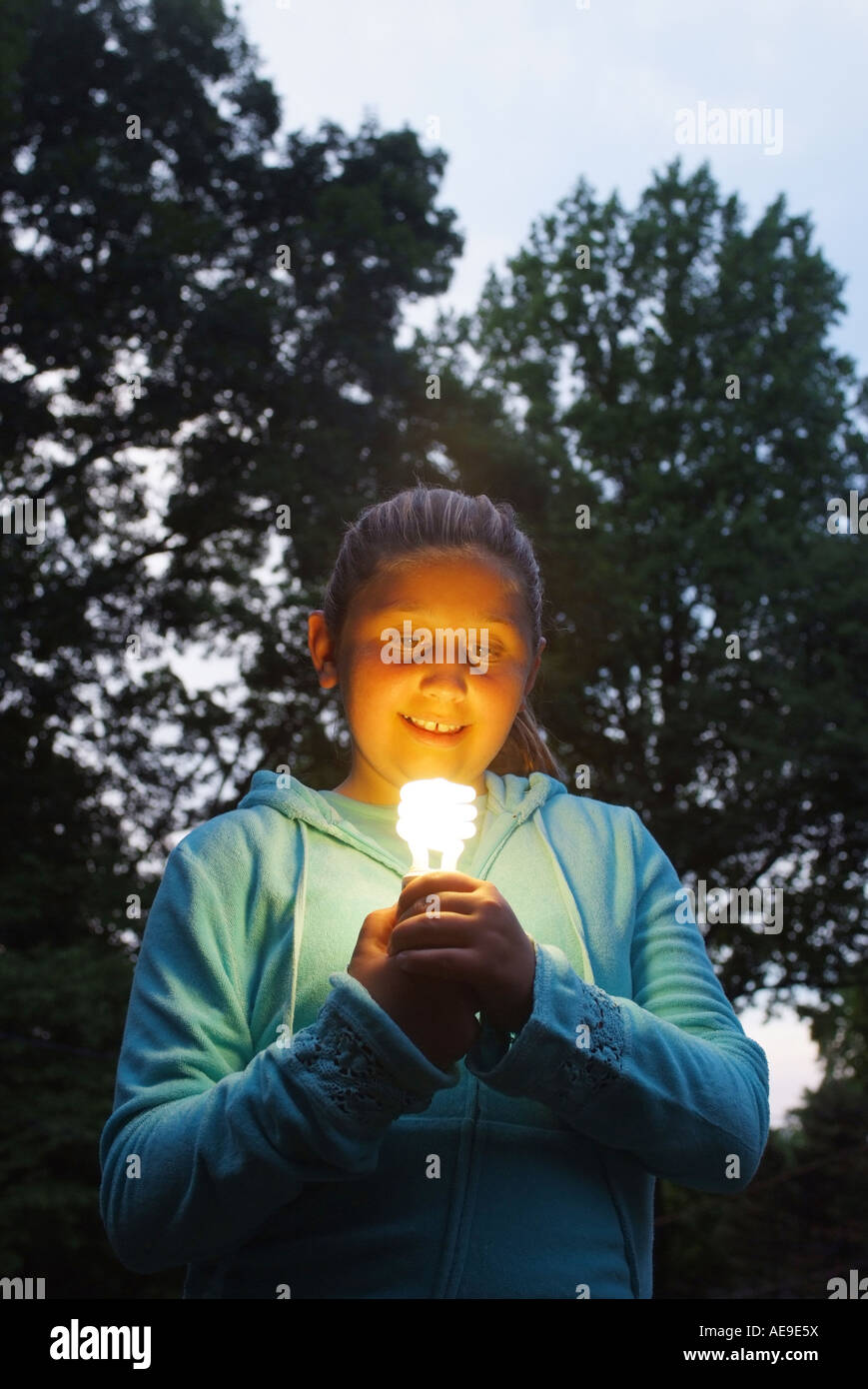 a-young-teenage-girl-holds-an-energy-saver-lightbulb-outdoors-AE9E5X.jpg