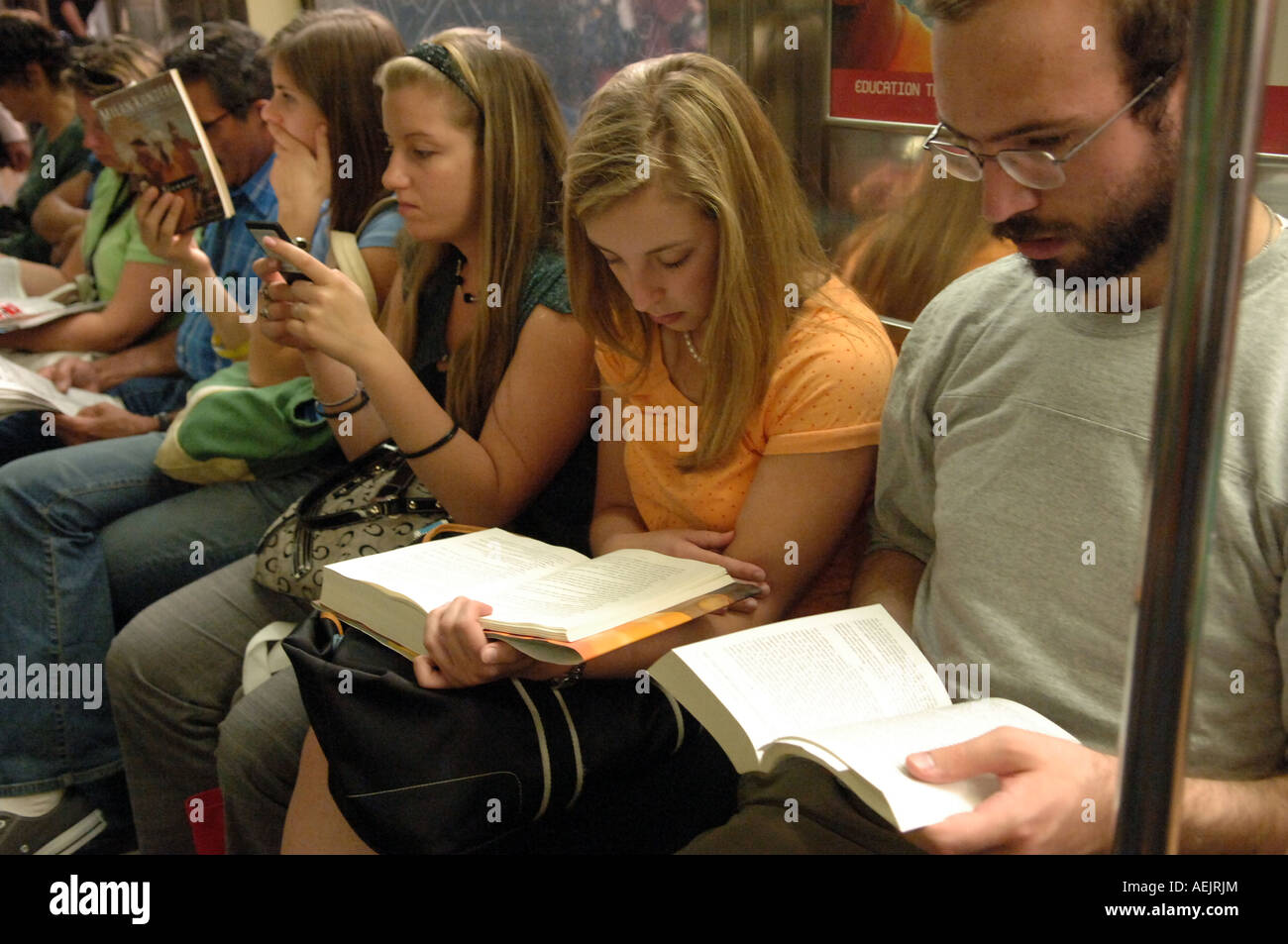 People reading on the subway in NYC - Stock Image