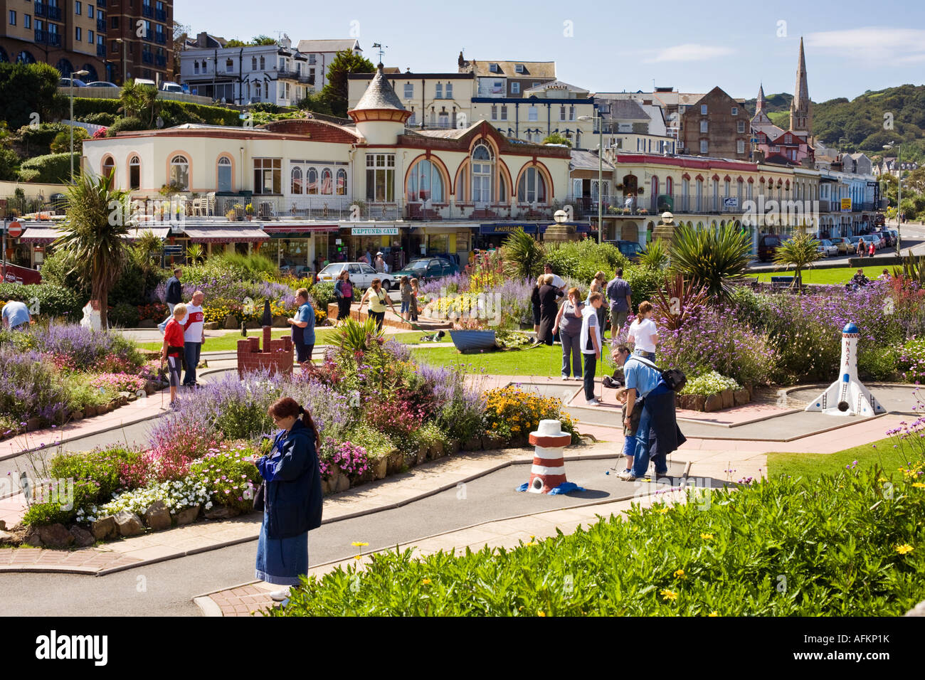 Tourists and holidaymakers playing Crazy Golf or Mini Golf at the seaside town on the promenade at Ilfracombe, Devon, - Stock Image