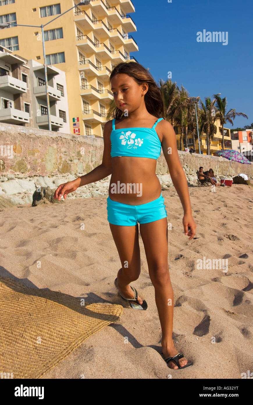 young mexican girl on a summer beach trip standing in sand