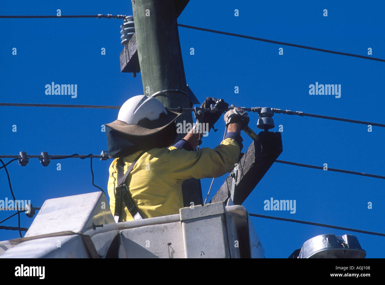 electricity-worker-in-elevated-work-platform-fixing-powerlines-AGJ108.jpg