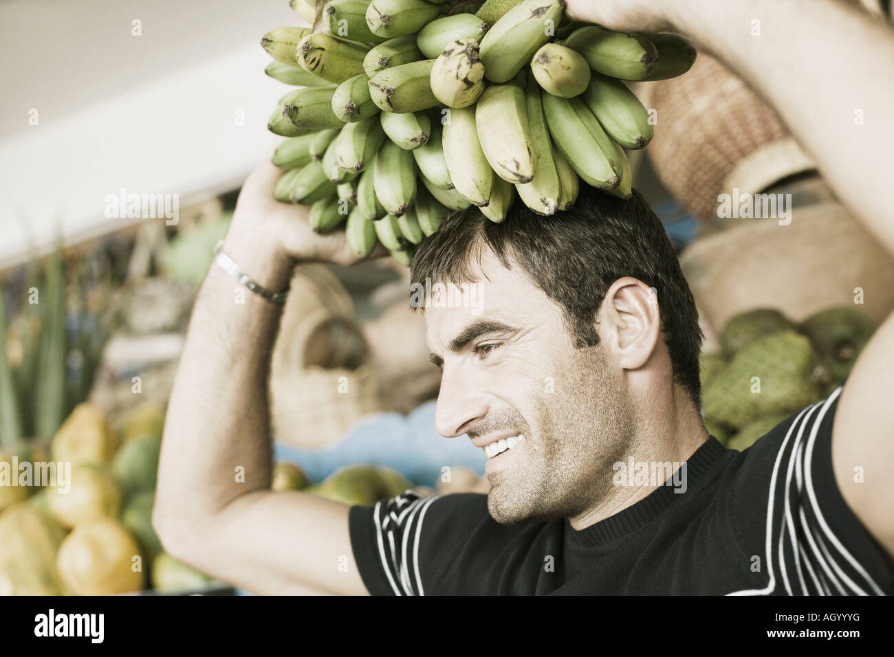 Close-up of a mid adult man carrying a bunch of bananas on his head - Stock Image