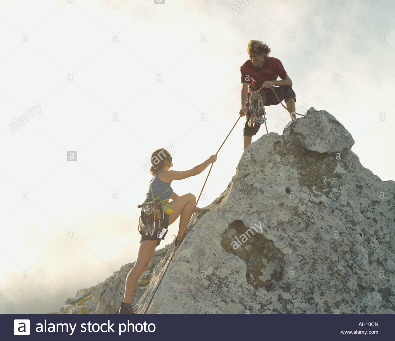A man helping a woman climber to the top of the mountain - Stock Image