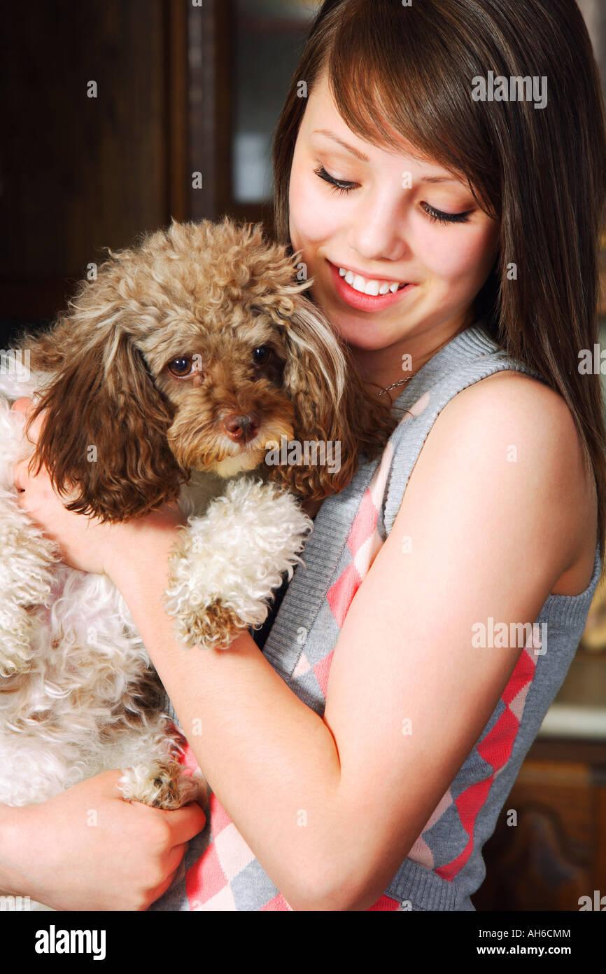 Teen girl holding dog - Stock Image