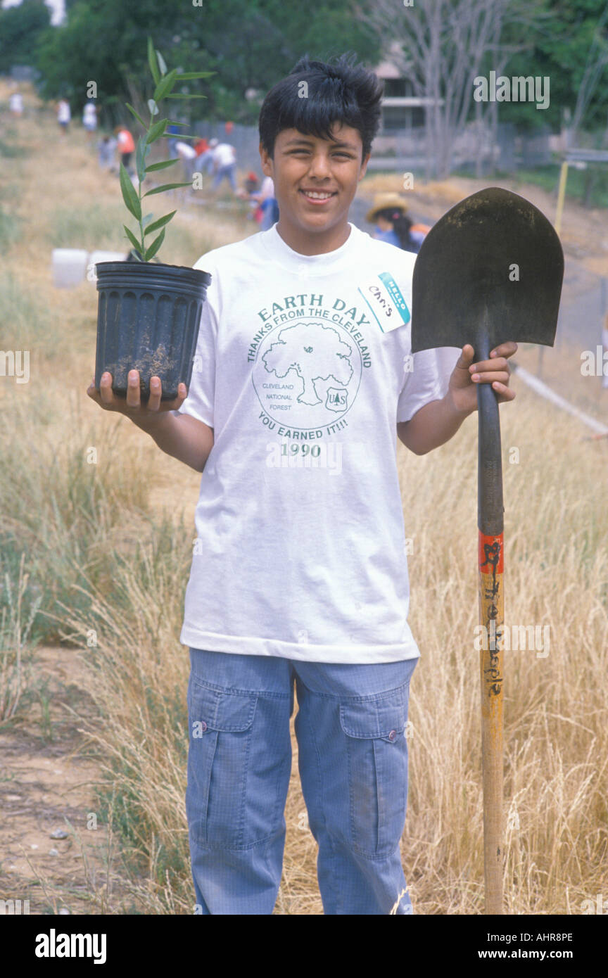 A teenage boy holding a plant and a shovel during Earth Day participation - Stock Image