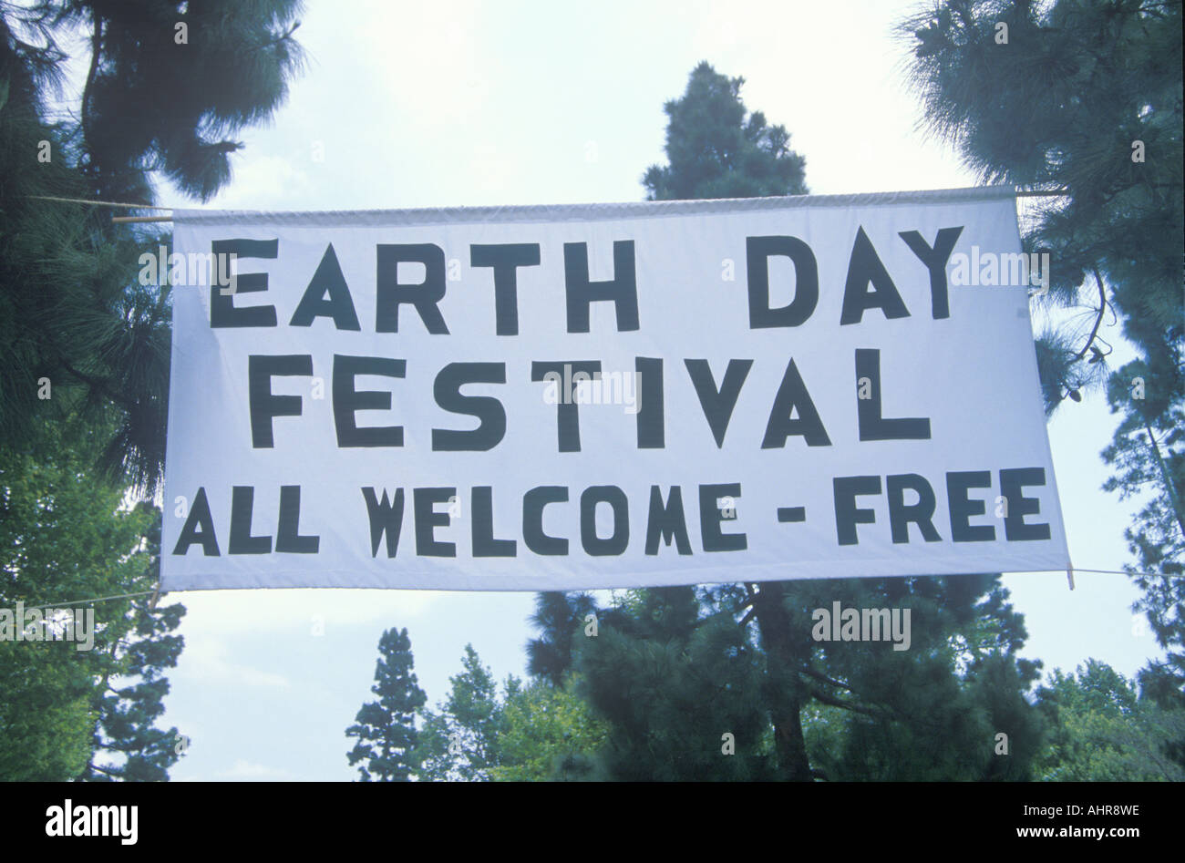 A hanging sign welcoming people to the Earth Day Festival - Stock Image