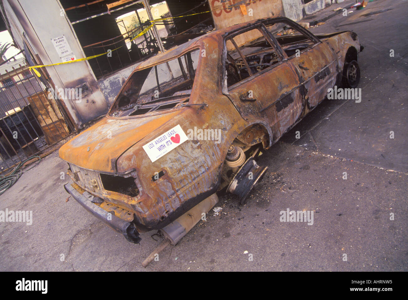 Car burned during 1992 riots South Central Los Angeles California - Stock Image