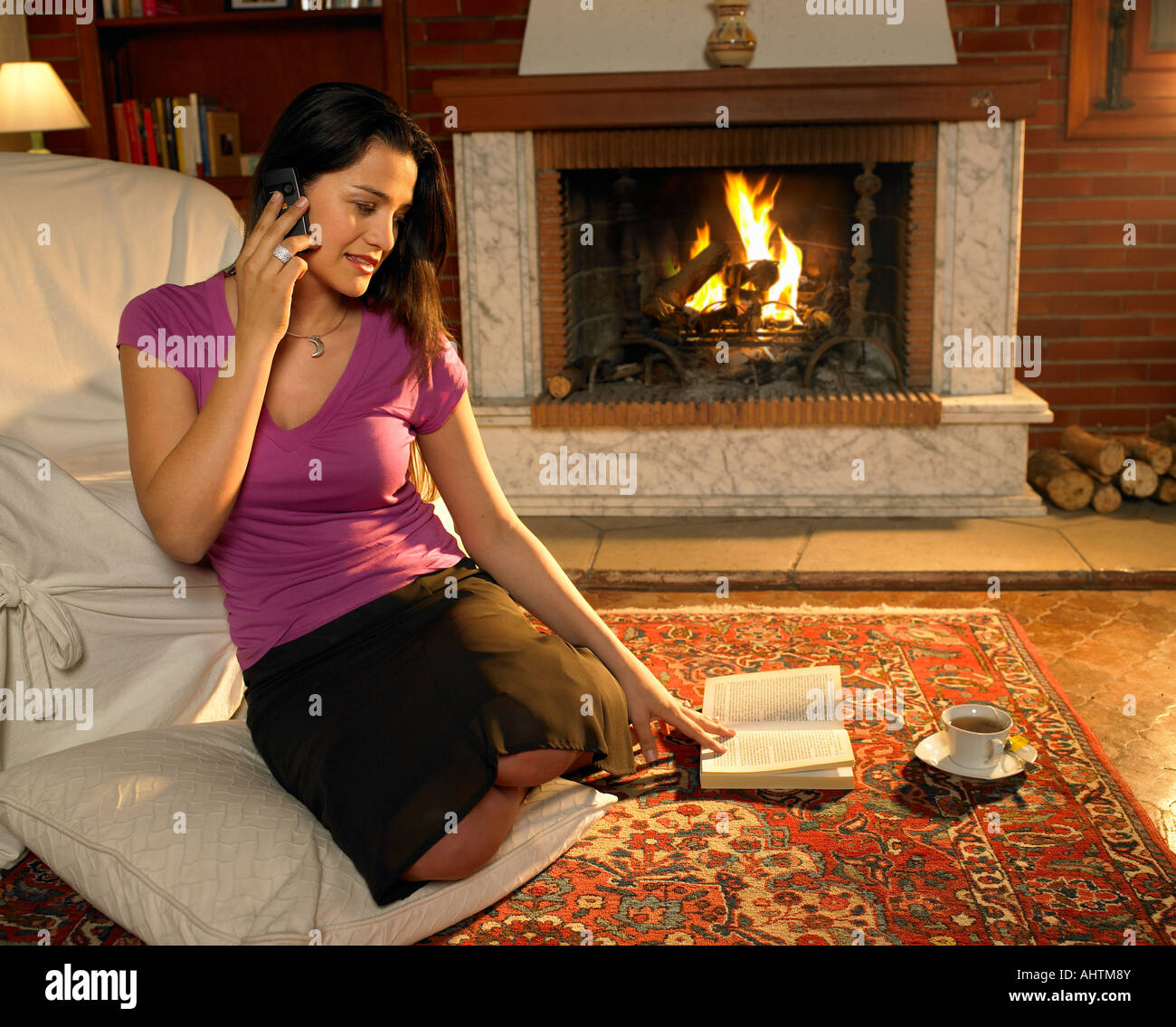 Young Woman Sitting On Rug In Front Of Fire Using Mobile