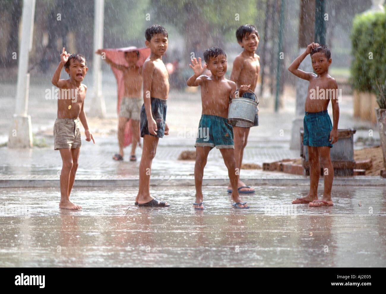 https://c7.alamy.com/comp/AJ2E05/boys-waving-and-playing-in-pouring-monsoon-rain-phnom-penh-cambodia-AJ2E05.jpg