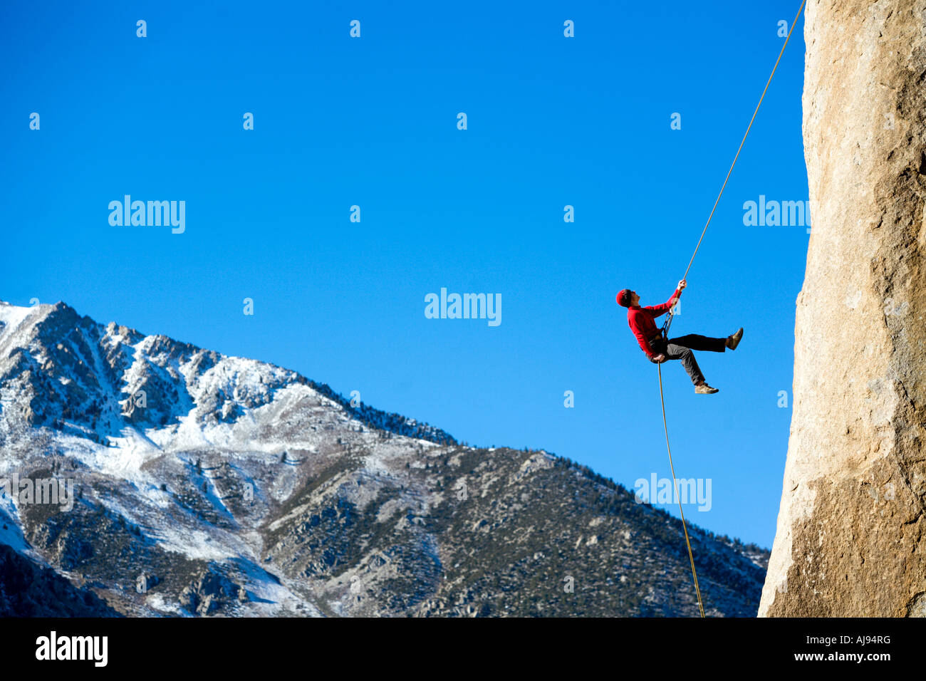 Climber rappelling down boulder - Stock Image