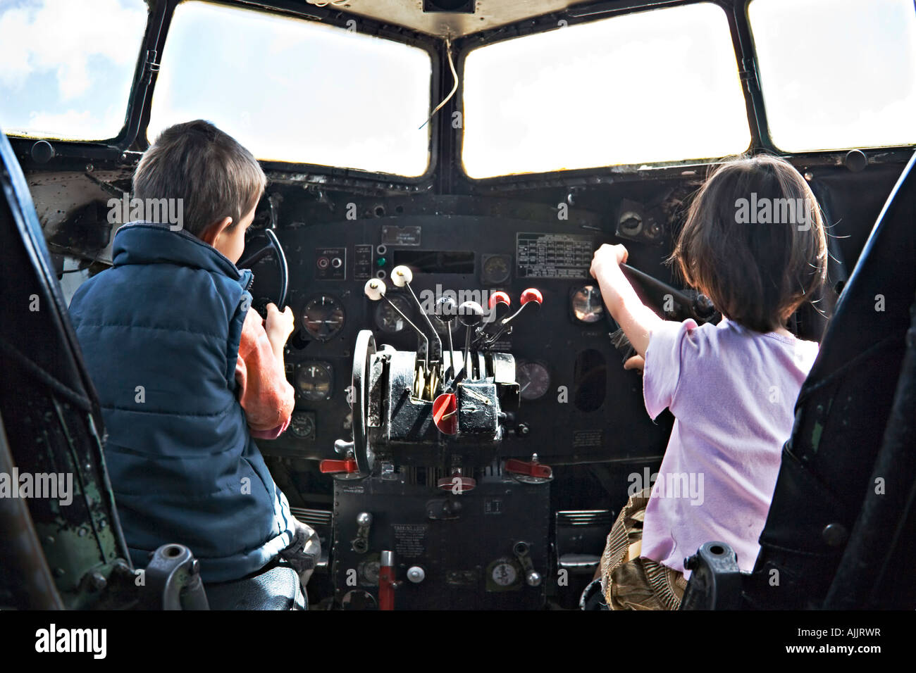 Boy and girl play in cockpit of old DC 3 Douglas Dakota - Stock Image