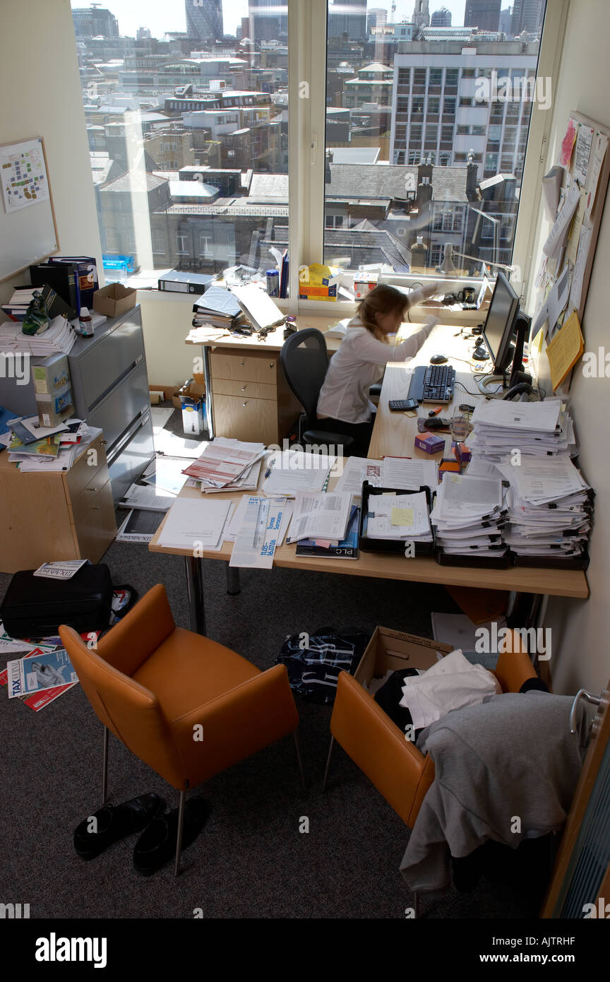Office life and interiors part two Messy office over looking the city with stressed employee at desk - Stock Image