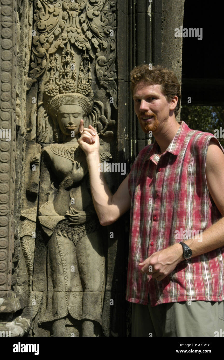 MR tourist is standing beside a stone relief of fine arts showing a charming - Stock Image