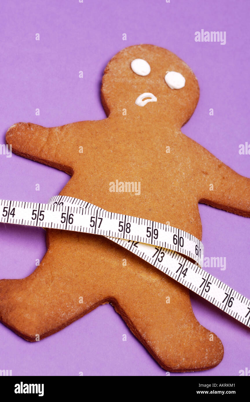 Gingerbread man with tape measure around waist Stock Photo
