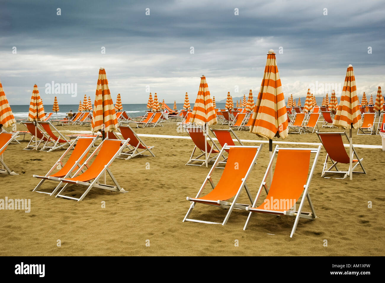 Orange deckchairs on a deserted beach in Viareggio Italy - Stock Image