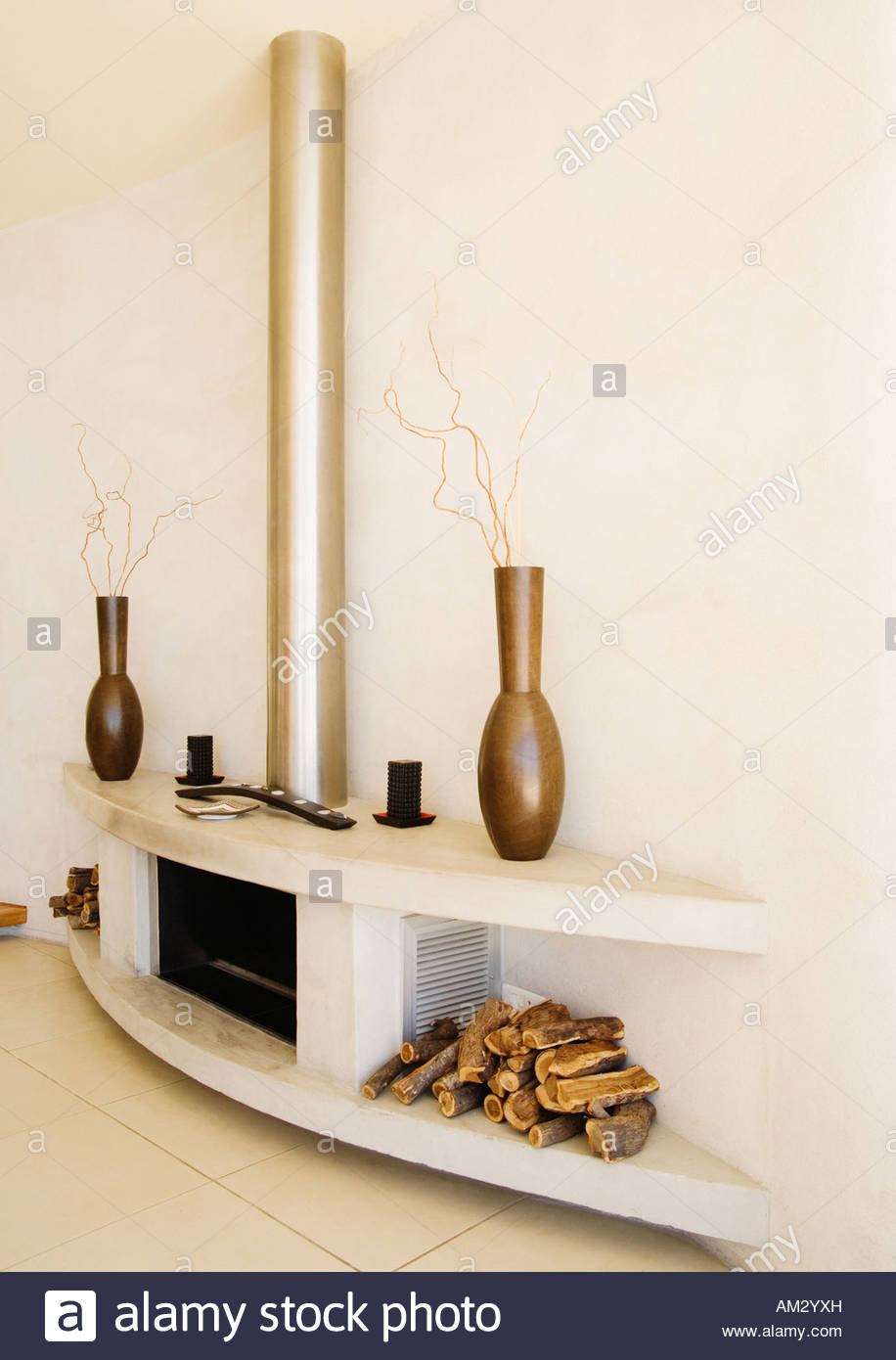 Modern fireplace with wood piles on each side - Stock Image