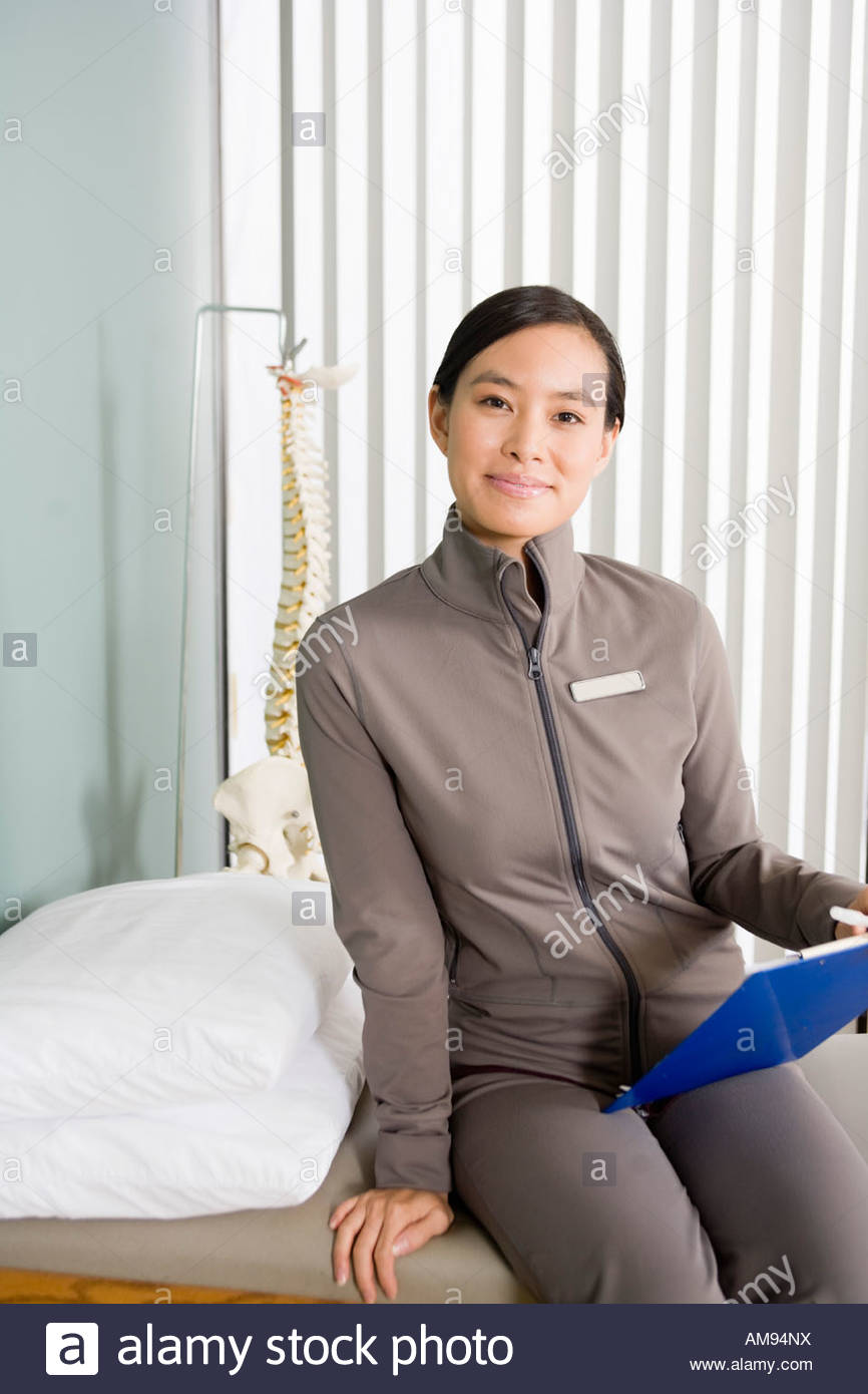 Asian female physical therapist holding chart
