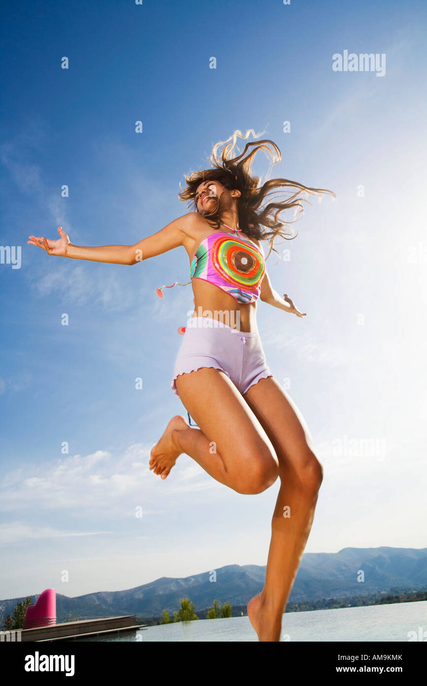 Woman jumps in air arms out wearing shorts outside. - Stock Image