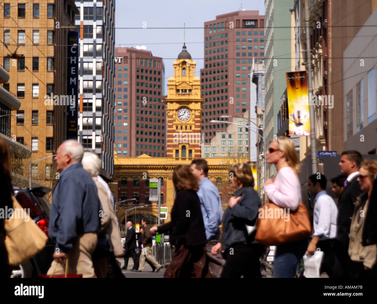 Lunchtime office workers crossing street in downtown Melbourne with Flinders Street railway station in background Stock Photo