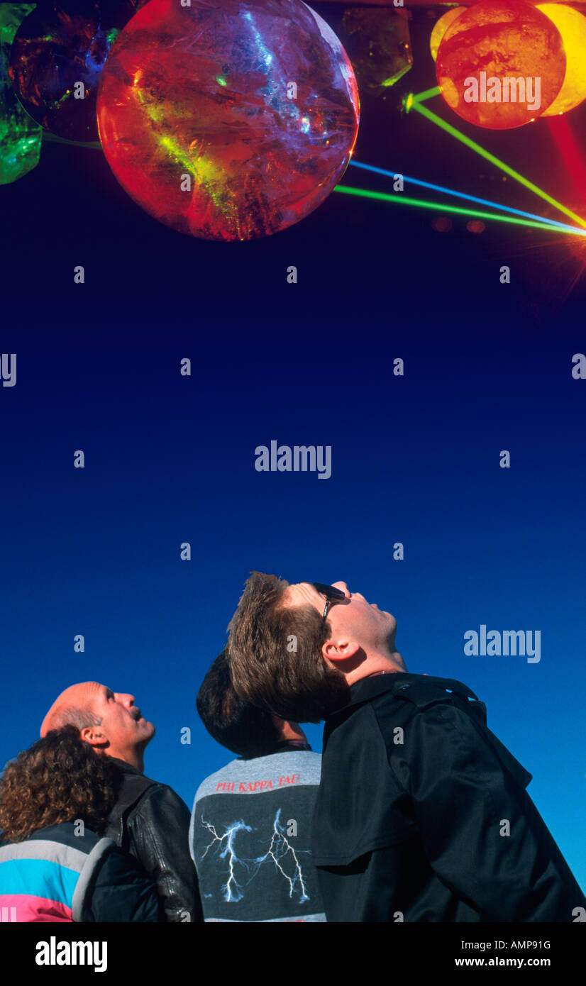Composite image of spectators looking up at planets and stars in the dark blue sky - Stock Image