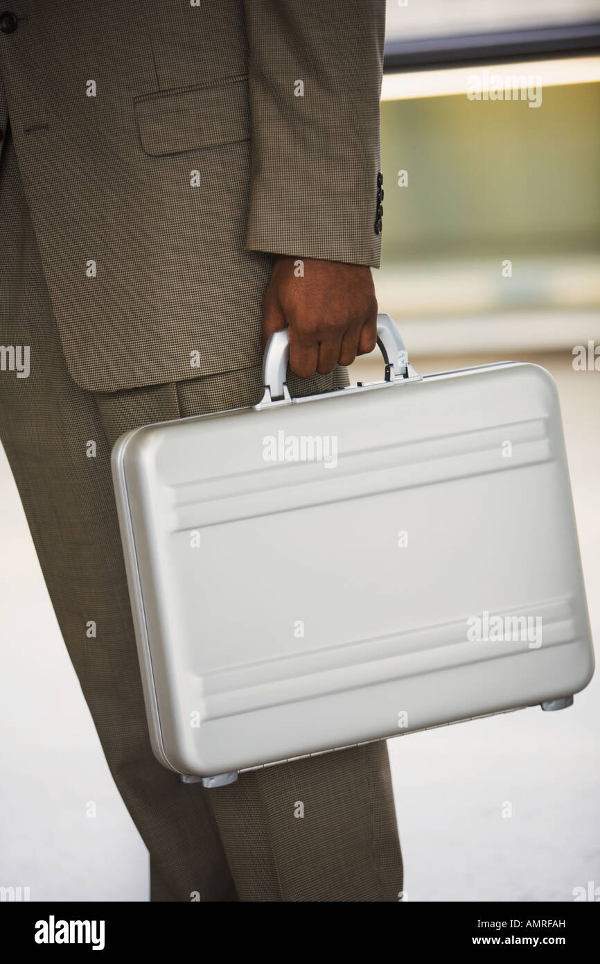 African businessman holding briefcase - Stock Image