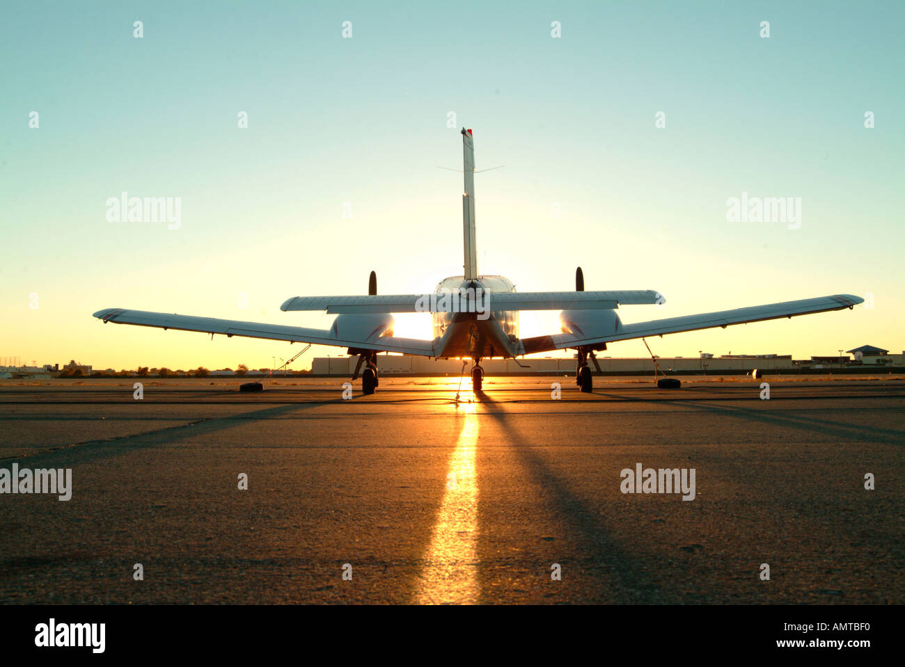 A twin engine plane on the tarmac at sunset - Stock Image