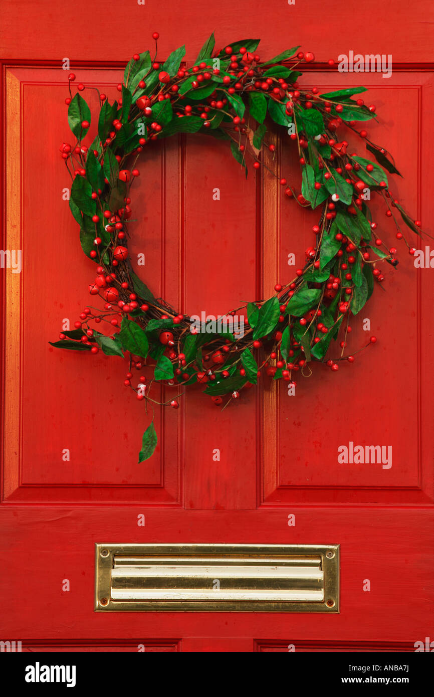 Christmas Holly Wreath On Distinctive Red Door Of Residential Home