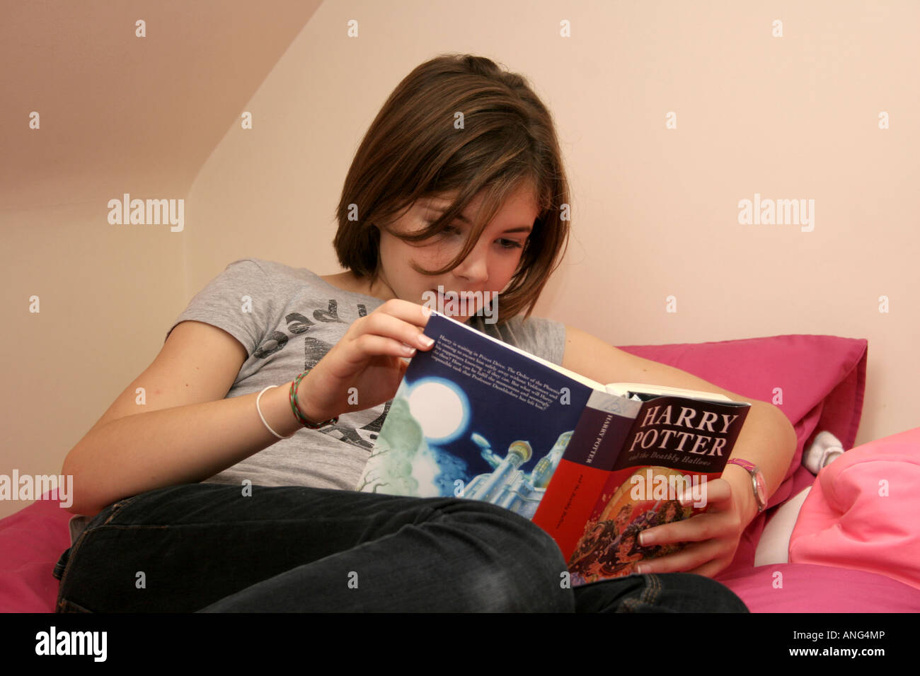 A teenage girl reading the final Harry Potter book. - Stock Image
