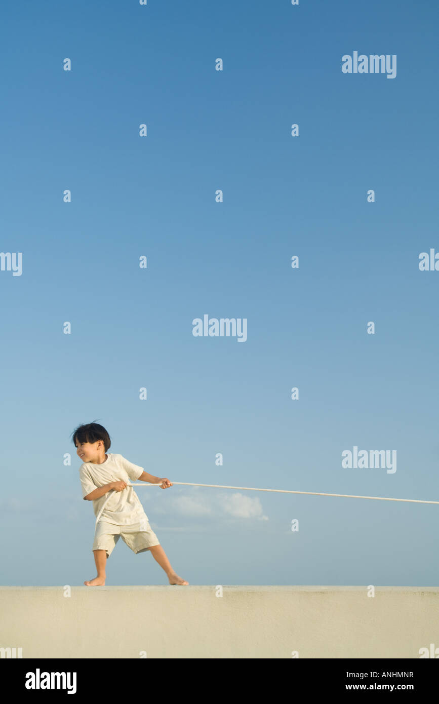 little boy pulling on rope, blue sky in background, full length
