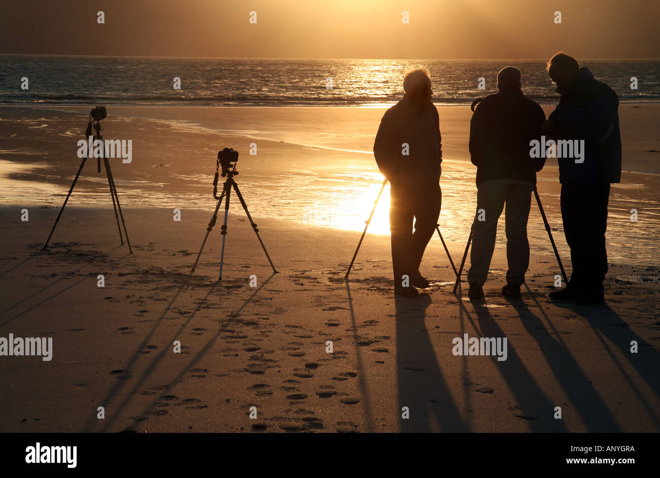 a-group-of-photographers-silhouetted-against-the-sunset-laig-bay-isle-ANYGRA.jpg