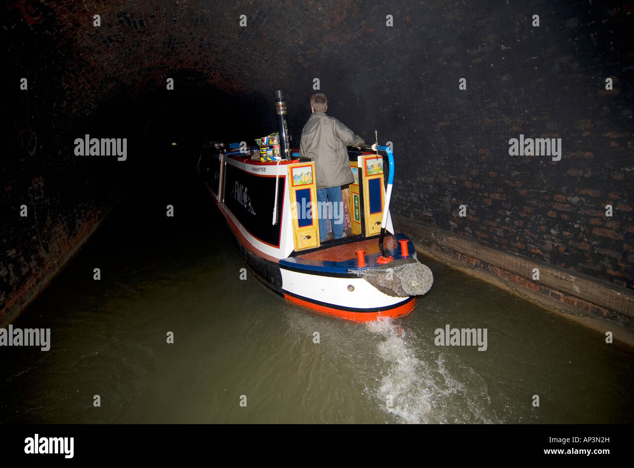Traditional narrowboat navigating through Blisworth Tunnel on the Grand Union canal - Stock Image