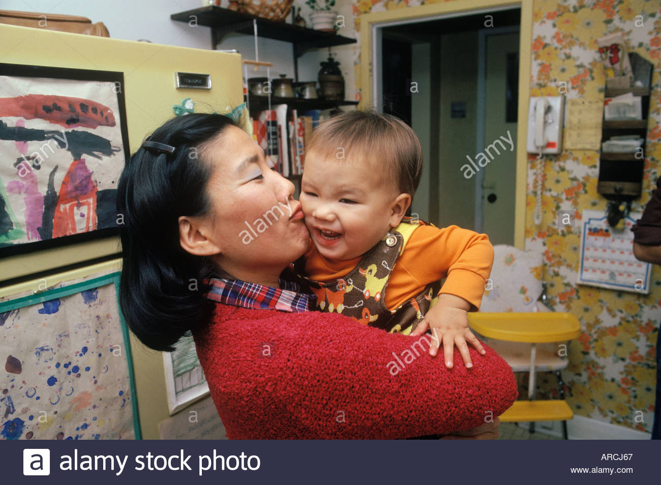 Aunt kissing and hugging squirming nephew in Toronto Ontario CanadaStock Photo