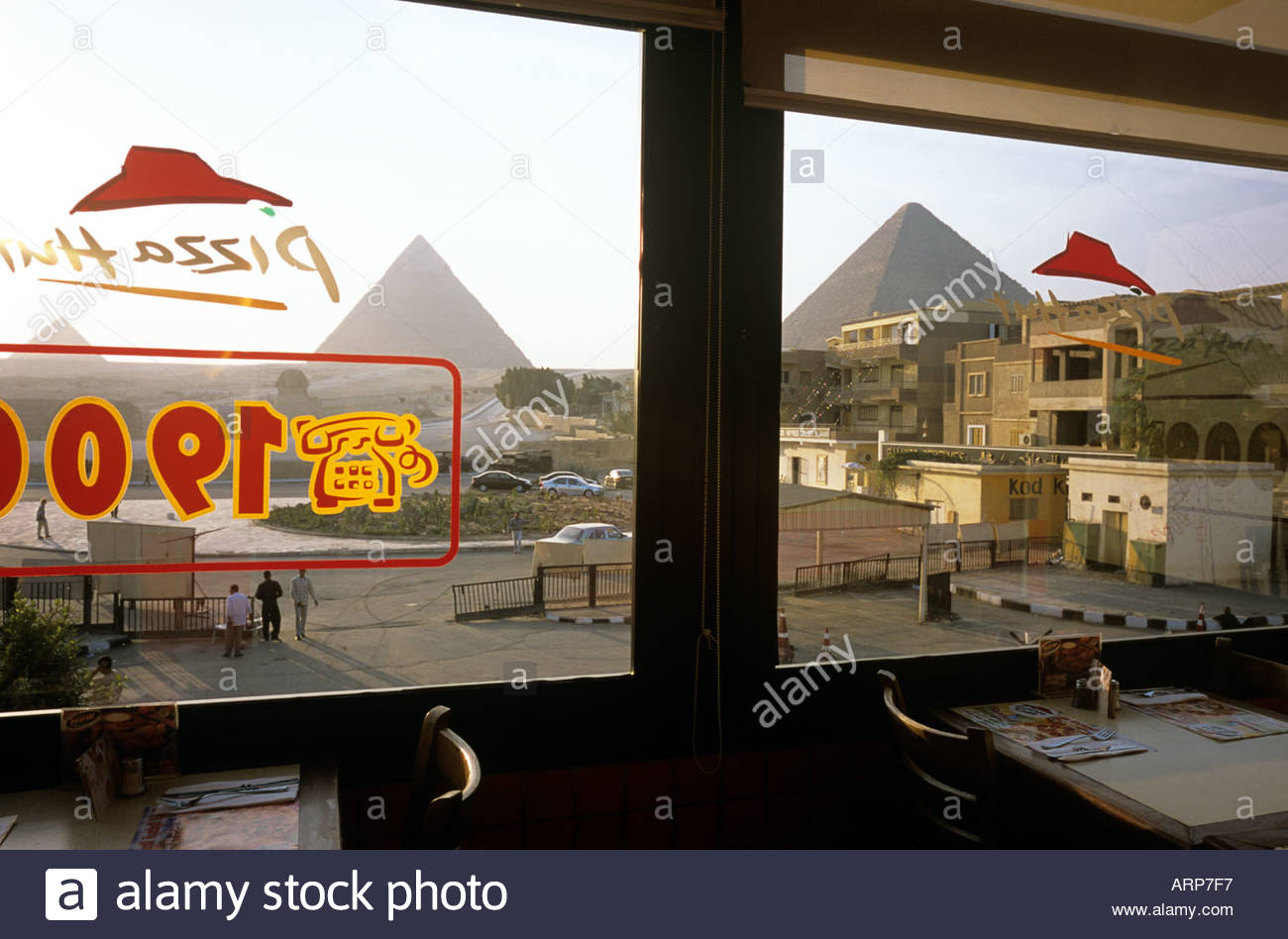 Pizza Hut restaurant in Giza Egypt, with the famous pyramids in the distance . October 2003 Stock Photo