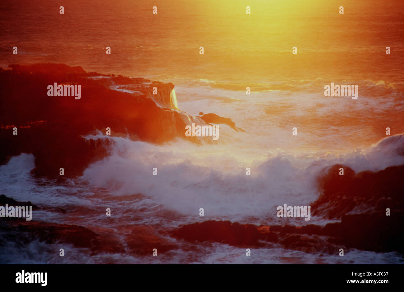 Waves breaking on rocky shoreline at sunset Piha New Zealand - Stock Image