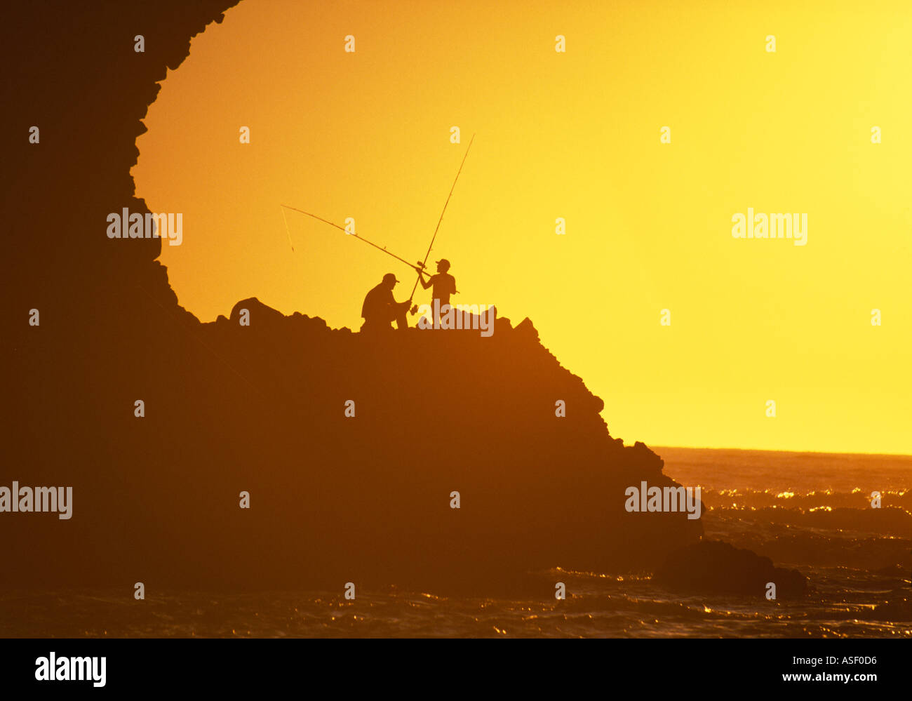 Fishermen on rocks at sunset Piha New Zealand - Stock Image