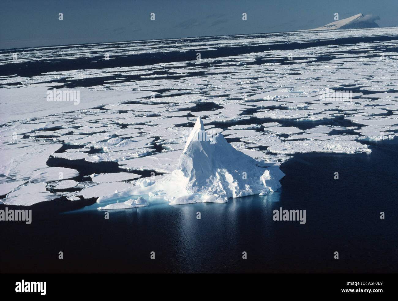 Aerial view of spired iceberg and pack ice sea ice Beaufort Island McMurdo Sound Ross Sea Antarctica - Stock Image