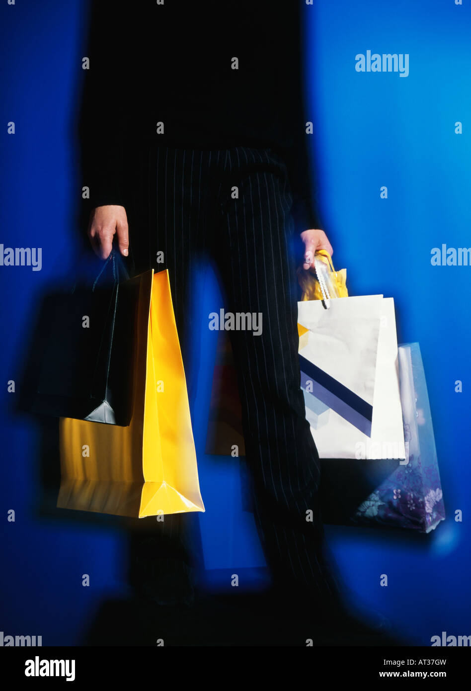 A man carrying shopping bags - Stock Image