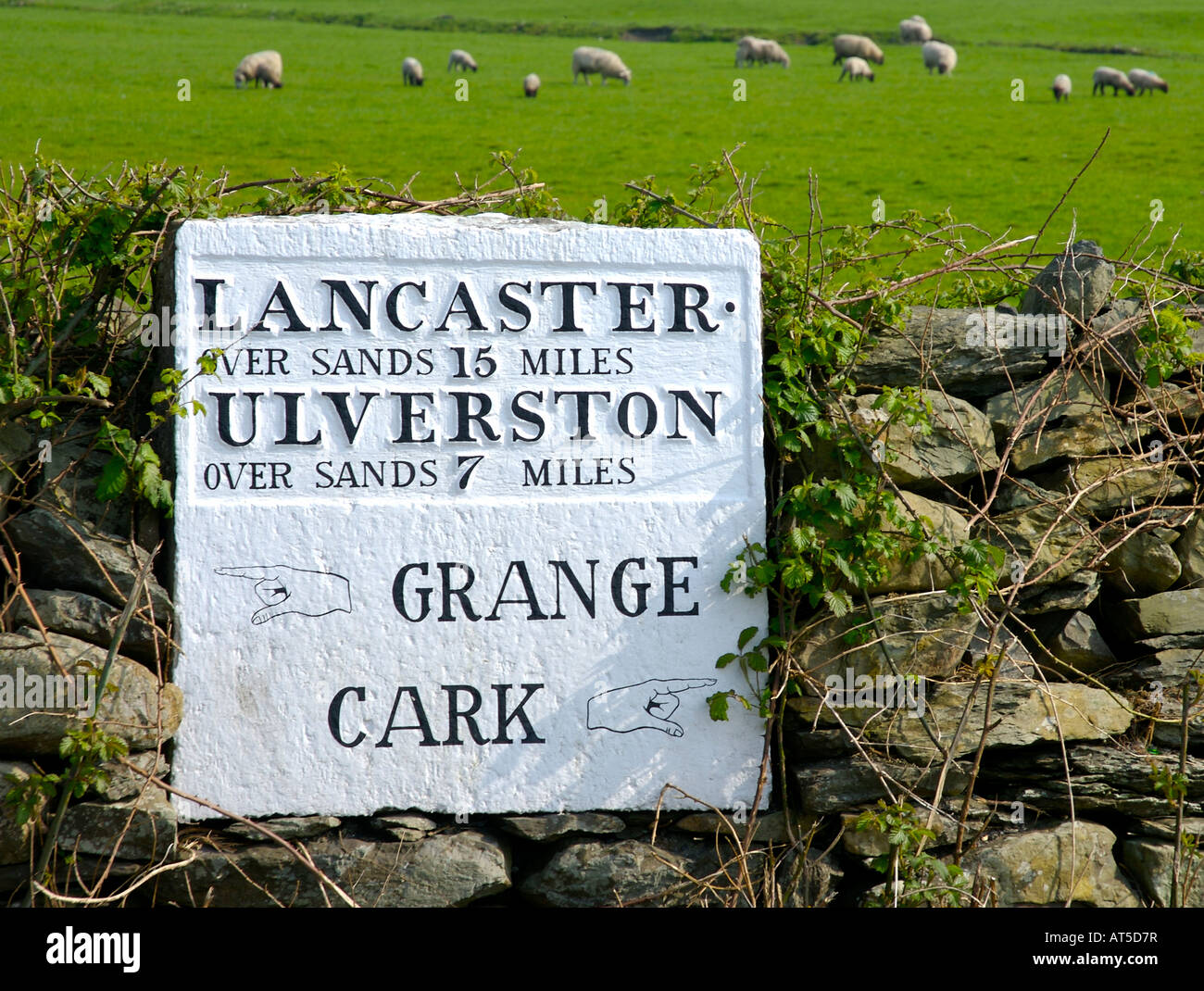 Old sign in Cartmel showing distances across the sands of Morecambe Bay, to Lancaster and Ulverston, Cumbria UK Stock Photo
