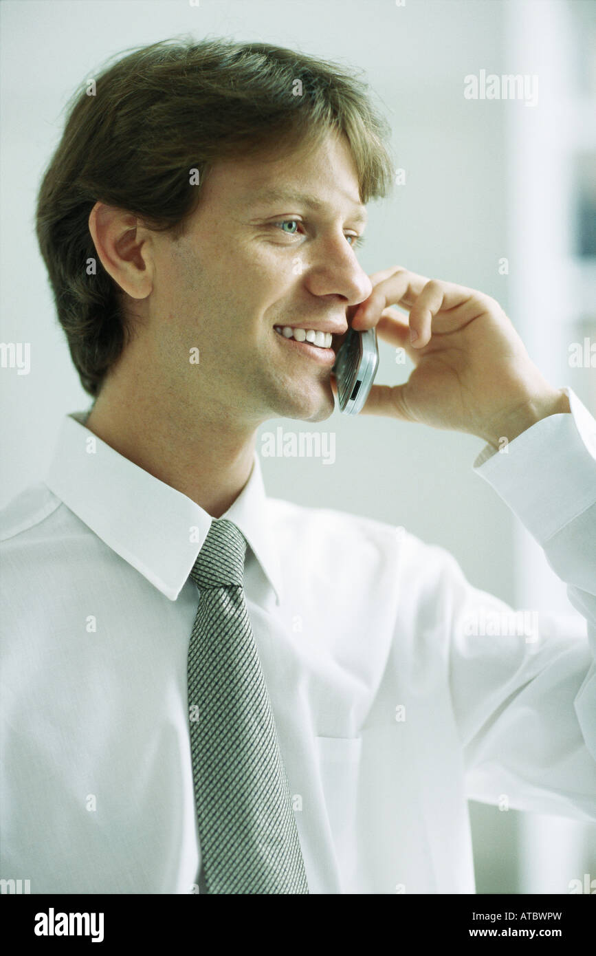 Businessman using cell phone, smiling, looking away - Stock Image