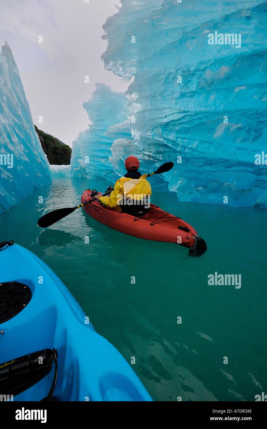 Exploring an iceberg by sea kayak in Tracy Arm Alaska Pacific Ocean - Stock Image