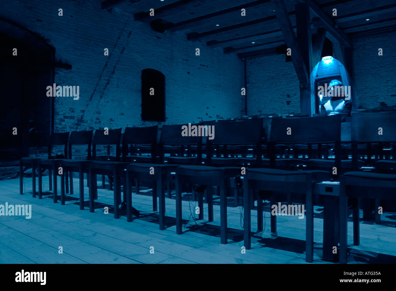 Man in an empty tumbledown cinema hall - Stock Image