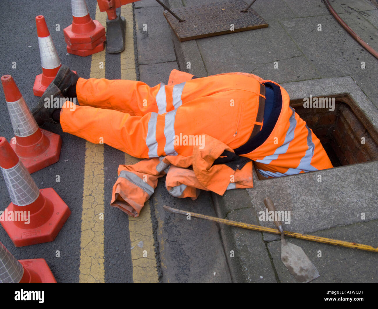 Dyno Rod worker wearing orange overalls  head first down a drain inspection chamber manhole looking for a blockage Stock Photo