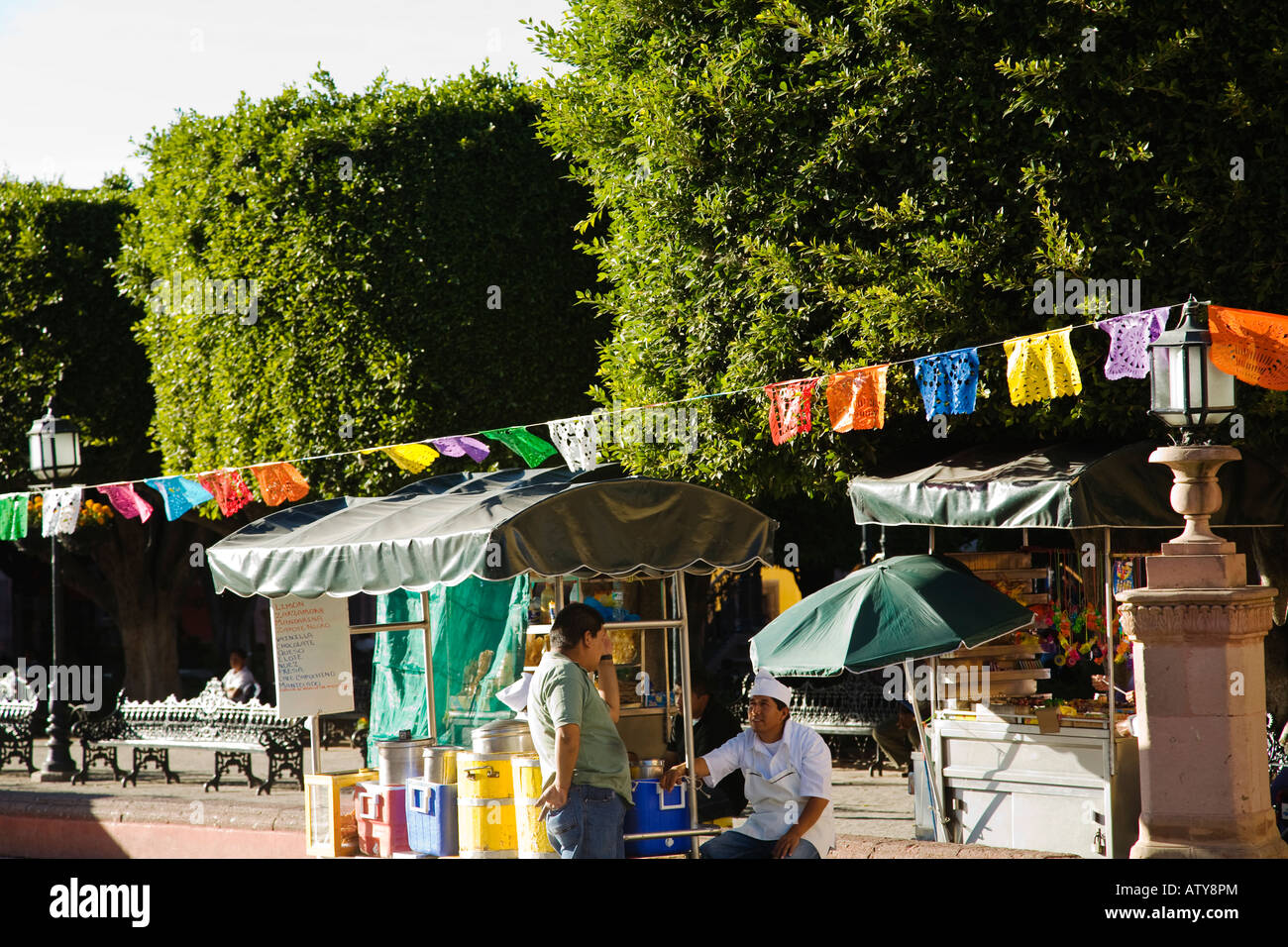 MEXICO San Miguel de Allende Cut out paper flags decorate plaza around El Jardin street vendors selling food and - Stock Image