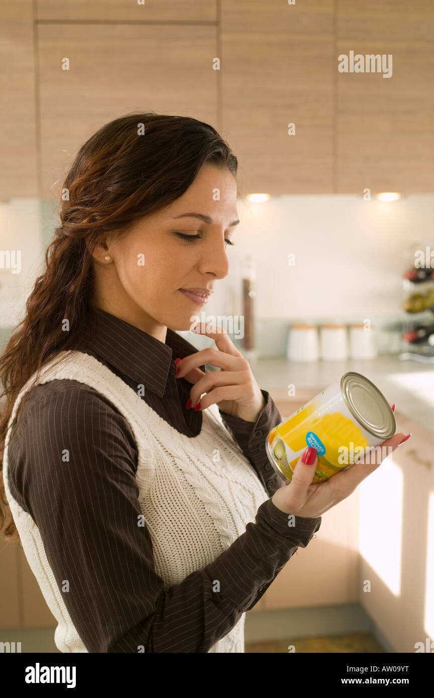 woman reading food label on a tin at home Stock Photo